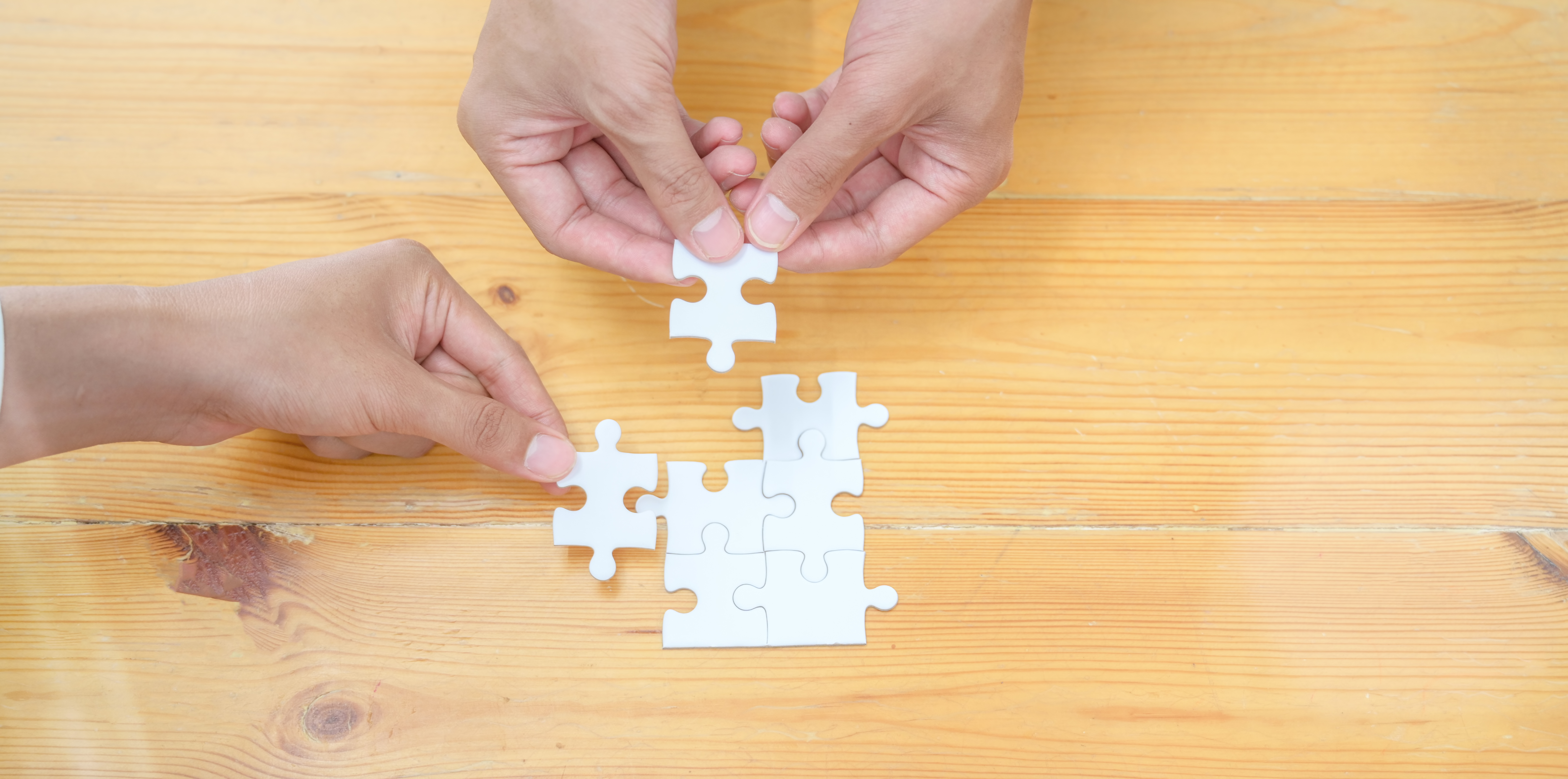 Top view of hands of diverse people assembling jigsaw puzzle
